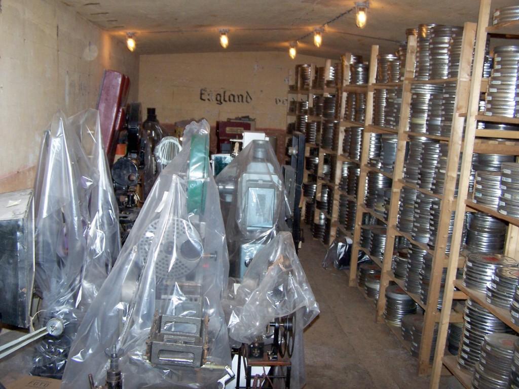 Opslag van brandbaar filmmateriaal en oude filmapparatuur in de kelder in november 2006. Op de achterwand is nog een deel van de tekst zichtbaar: England Verrecke. Linksboven aan het plafond zijn nog de inmiddels weggeslepen beugels te zien waar eens de uitschuifbare rekken aan gemonteerd waren .(foto T.W. Spruyt)